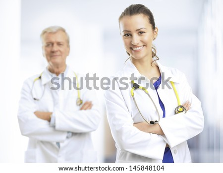Smiling young female doctor standing with arms crossed in hospital ward Her colleague in the background