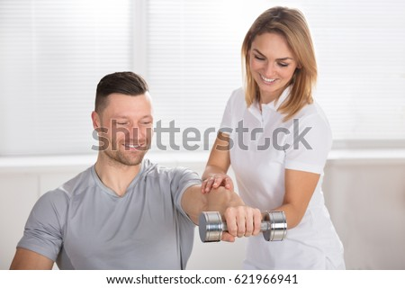 Smiling Young Female Physiotherapist Helping Man To Exercise With Dumbbell