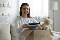 Smiling young female put stack things clothes in cardboard box, make donation to poor needy people, happy millennial woman volunteer donate things apparel in charity parcel, reuse, recycle concept