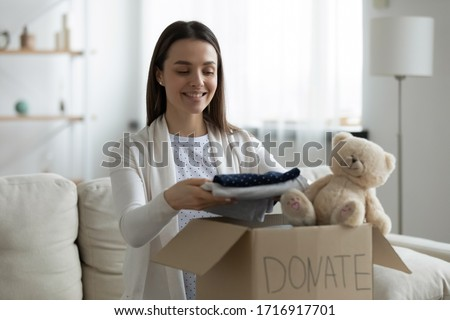 Smiling young female put stack things clothes in cardboard box, make donation to poor needy people, happy millennial woman volunteer donate things apparel in charity parcel, reuse, recycle concept Stock photo ©