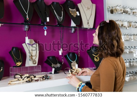Smiling young female wants to buying different pendants in the market #1560777833