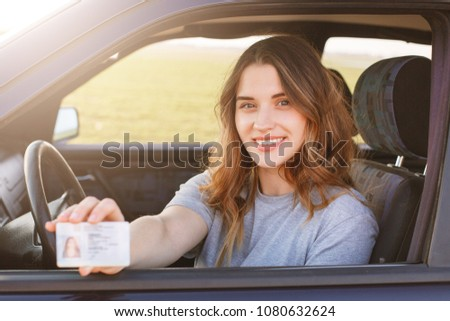 Smiling young female with pleasant appearance shows proudly her drivers license, sits in new car, being young inexperienced driver, looks with joyful expression. I get it finally! Successful woman