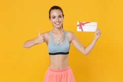 Smiling young fitness sporty woman in sportswear working out isolated on yellow background. Workout sport motivation lifestyle concept. Mock up copy space. Hold gift certificate showing thumb up