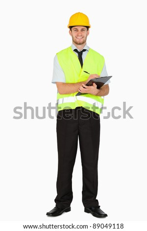 Smiling young foreman in safety jacket taking notes on his clipboard against a white background