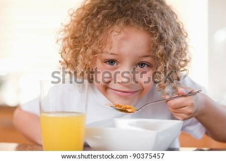 Smiling young girl having breakfast