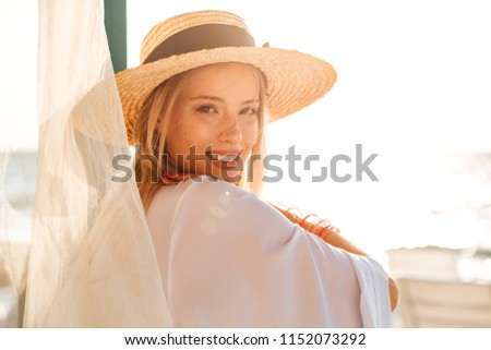 85134baecf7d5 Smiling young girl in summer hat and swimwear resting at the sunny beach
