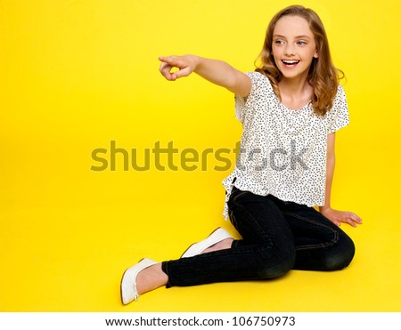 Smiling young girl pointing away. Sitting on floor