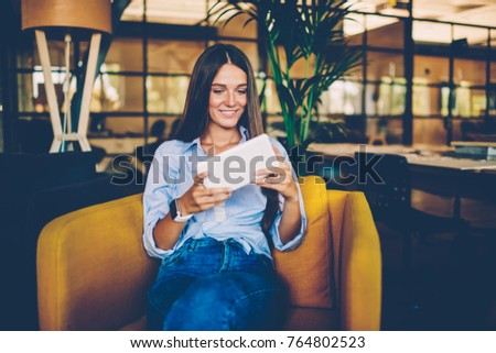 Smiling young girl resting in cozy chair using digital tablet playing games online feeling excitement passing next level, positive brunette woman looking at web store page choosing item for shopping