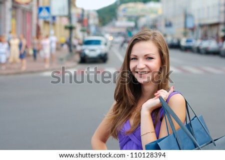 Smiling young girl shopping outdoors