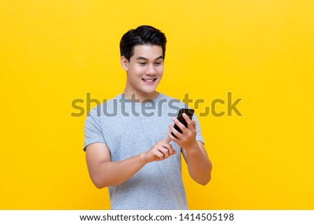 Smiling young good looking Asian man using smartphone to get in touch with family and friends isolated on bright yellow studio background