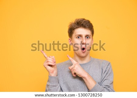 Smiling young guy is standing on a yellow background and showing his fingers on copyspace. Positive man shows his hands aside and looks at the camera, isolated on a yellow background. #1300728250