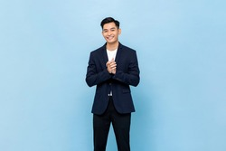 Smiling young handsome southeast Asian man clapping hands impressively in light blue studio isolated background