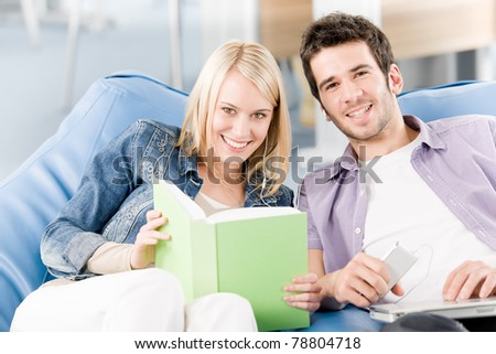 Smiling young high-school students reading book listen music