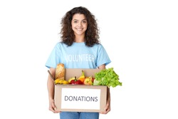 Smiling young hispanic latin woman courier wears volunteer tshirt look at camera hold social donations box concept delivering grocery food delivery stand isolated on white studio background. Portrait.
