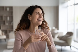 Smiling young Hispanic woman hold glass enjoy clean mineral water look in distance dreaming visualizing. Happy millennial Latino female feel dehydrated drink aqua. Healthy lifestyle, habit concept.
