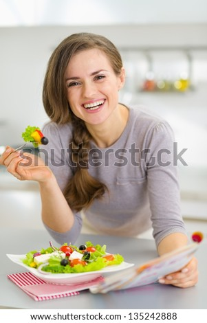 Smiling young housewife eating fresh salad and reading magazine in kitchen #135242888