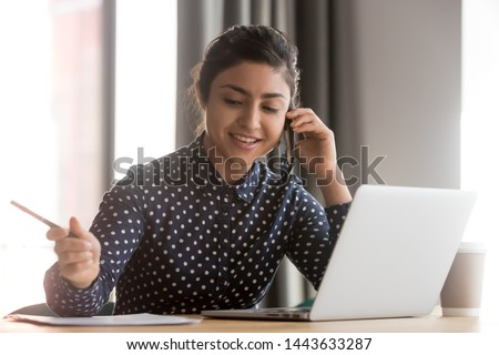 Smiling young indian business woman talk on phone write note sit at office desk, female hindu professional secretary receptionist hold cellphone consult client make mobile call at corporate workplace