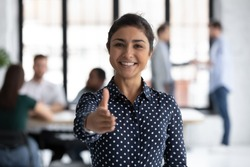 Smiling young Indian businesswoman look at camera stretch hand welcome new employee at workplace, happy biracial female recruiter meeting greeting newcomer newbie in office, employment concept