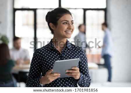 Smiling young Indian female employee hold tablet look in distance thinking, happy millennial biracial woman worker distracted from pad gadget, lost in thoughts visualizing, business vision concept