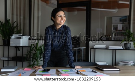 Smiling young indian female employee stand at desk in office look in distance thinking or visualizing career success. Happy ethnic businesswoman plan or dream at workplace. Business vision concept.