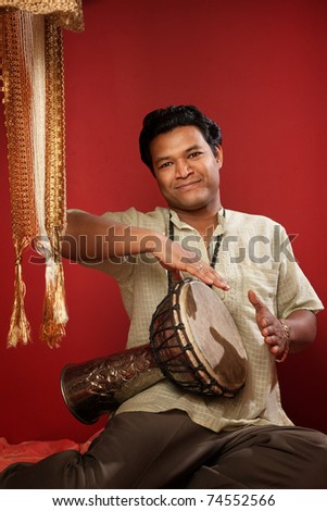 Smiling young Indian man playing a tabla