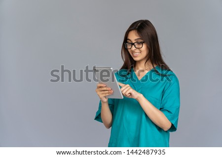 Smiling young indian woman professional nurse female doctor wear green uniform glasses holding using digital tablet isolated on grey studio background, healthcare technology concept, copy space