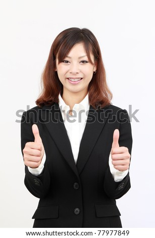 Smiling young japanese business woman showing thumbs up gesture