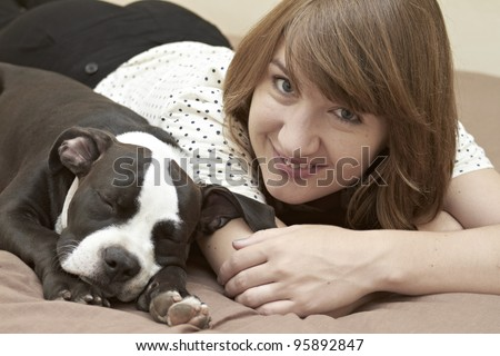Smiling young lady and her sleeping Pit Bull puppy