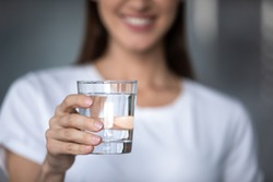 Smiling young lady holding fresh transparent pure filtered mineral water, happy healthy adult woman offering glass to camera as health care thirst hydration natural nutrition concept, close up view