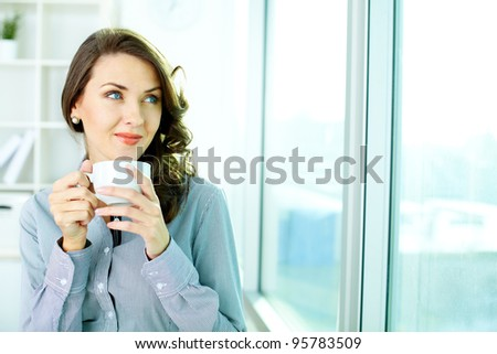 Smiling young lady looking in the window at office - stock photo