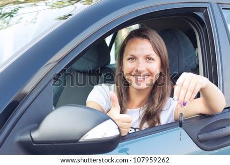 Smiling young lady sitting in a car and showing key
