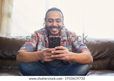 Smiling young latino man in his thirties sitting on his couch at home using his smart phone. Background unfocus  Stockfoto ©
