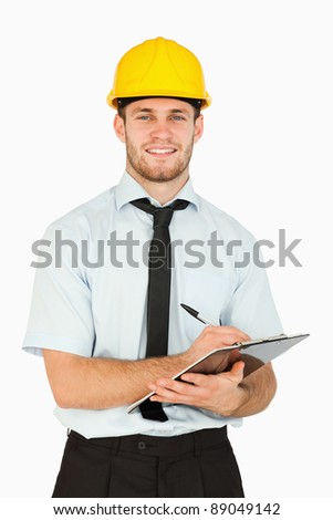 Smiling young lead worker taking notes on his clipboard against a white background