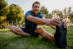 Smiling young male athlete sitting down stretching while listening to music in ear phones before exercising outdoors in park
