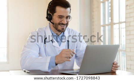 Smiling young male doctor in white medical uniform and wireless headset talk on video call on computer, consult patient online, happy Caucasian man GP in headphones watch webinar on laptop in hospital