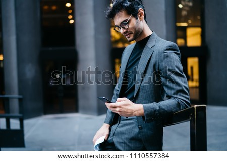 Smiling young male executive manager in trendy clothes using mobile phone outdoors,prosperous businessman i elegant formal suit sending text messages via smartphone connected to 4G internet