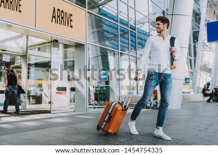 Smiling young male is leaving airport with luggage. He is looking back with pleasure while listening to music via earphones. Copy space in left side