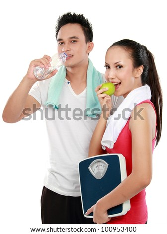 Smiling young man and woman with water and apple. diet fitness concept Isolated over white background