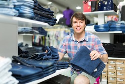 Smiling young man choosing new pair of blue jeans at the store