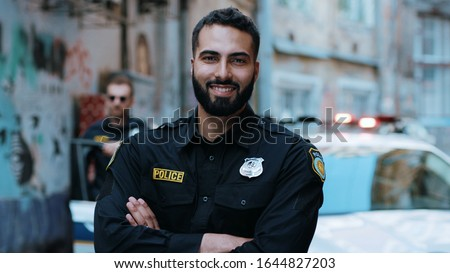 Smiling young man cops stand near patrol car look at camera enforcement happy officer police uniform auto safety security communication control policeman portrait close up slow motion Stock fotó ©