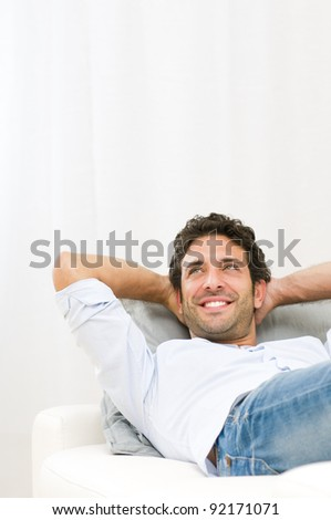 Smiling young man dreaming at his future and relaxing on sofa at home
