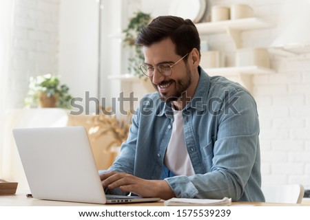 Smiling young man freelancer using laptop studying online working from home, happy casual millennial guy typing on pc notebook surfing internet looking at screen enjoying distant job sit at table