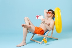 Smiling young man guy in orange shorts glasses sit on deck chair isolated on pastel blue background studio. People summer vacation rest lifestyle concept. Mock up copy space. Hold gift certificate