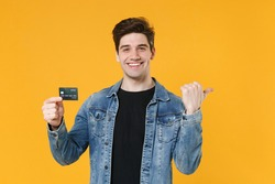 Smiling young man guy 20s in casual denim jacket posing isolated on yellow background studio portrait. People lifestyle concept. Mock up copy space. Holding credit bank card, pointing thumb aside