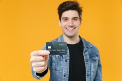 Smiling young man guy 20s in casual denim jacket posing isolated on yellow wall background studio portrait. People sincere emotions lifestyle concept. Mock up copy space. Holding credit bank card