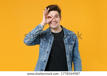 Smiling young man guy wearing casual denim jacket posing isolated on yellow background in studio. People lifestyle concept. Mock up copy space. Holding hand near eyes, imitating glasses or binoculars Stockfoto ©