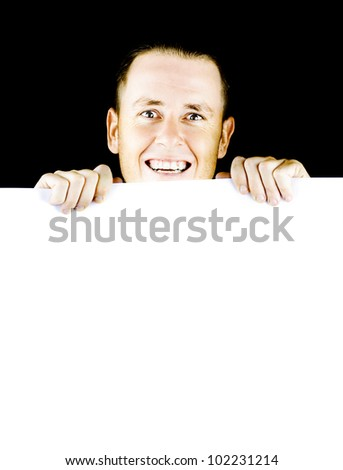 Smiling young man holding a blank poster board with space for your message or text