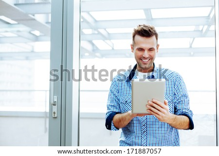 Smiling young man holding and using a digital tablet