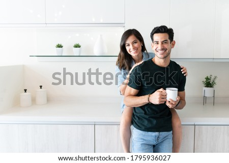 Smiling young man holding coffee mug while girlfriend sitting on kitchen counter
