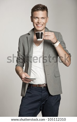 smiling young man holding cup of tea